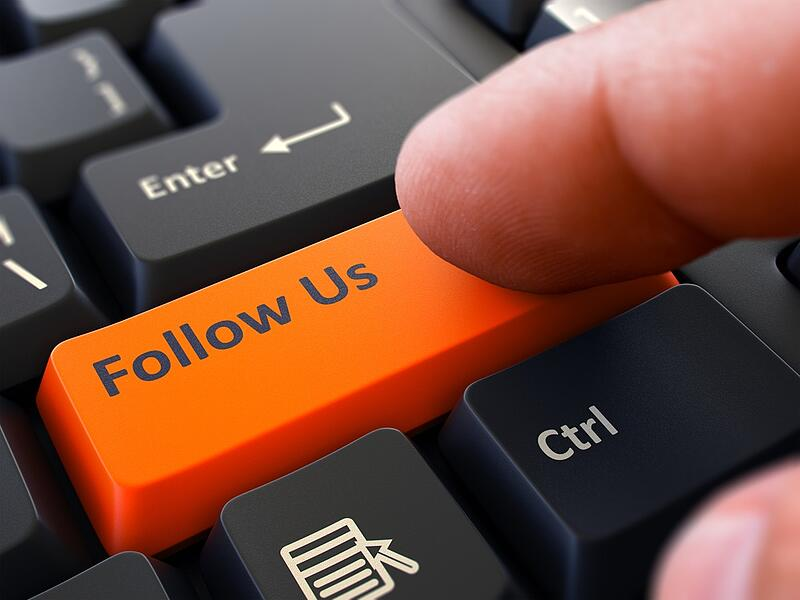 Follow Us Button. Male Finger Clicks on Orange Button on Black Keyboard. Closeup View. Blurred Background.
